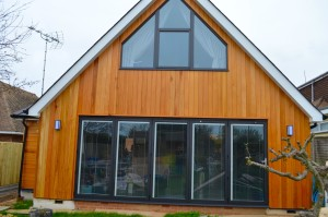 Amfchwand anthracite grey aluminium windows and doors and bifolds with integrated blinds and Hormann front door